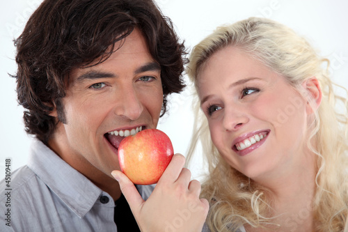 Woman looking at man eating an apple