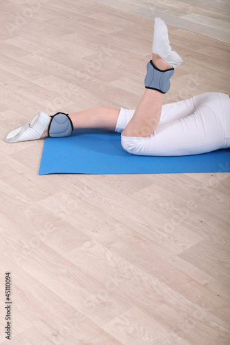 Woman using ankle weights on an exercise mast