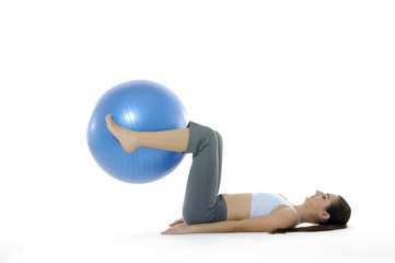 beautiful woman in gym outfit exercising with a pilates ball