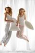 Couple girl holding pillow jumping on her bed