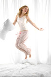 blond woman holding pillow jumping on her bed