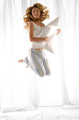 Young woman holding pillow jumping on her bed