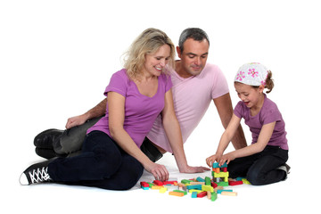 Parents and daughter playing building game