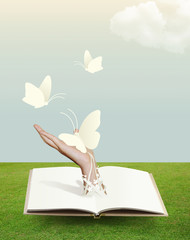 open book on grass with butterfly in hand.
