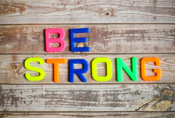 Be strong in colorful plastic letterpress on wood background