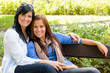 Mother and daughter relaxing on park bench