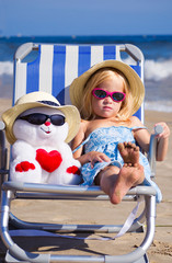 Ребенок сидит на шезлонге с игрушкой