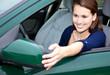 Junge Frau im Auto justiert ihren Seitenspiegel