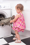 little baby reaching washed things out of washing machine