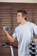Man Lifting Dumbbell In Health Center