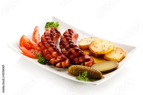 Grilled sausages, baked potatoes and vegetables