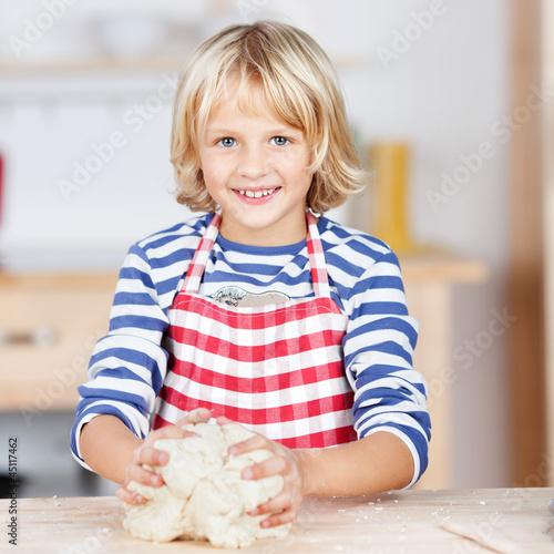 blondes mädchen knetet teig in der küche
