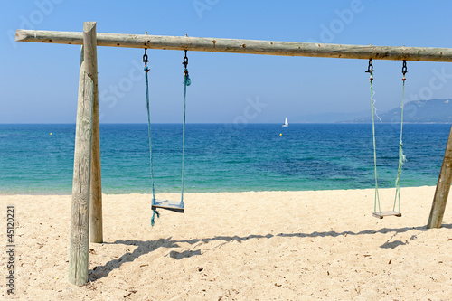 Double swing on beach by the sea