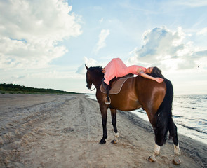 young  beautiful girl with horse on seacoast