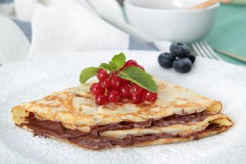 crespelle con cioccolata e frutta su piatto
