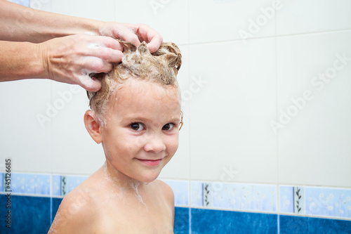 Cute four year old girl taking a relaxing bath with foam
