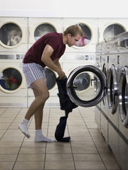 man taking off his clothes at a laundromat