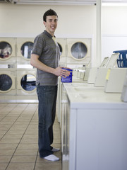 man doing laundry at a laundromat