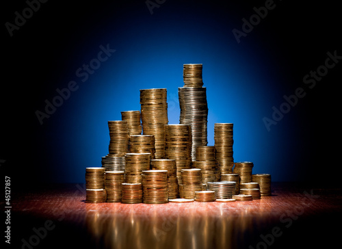 coins folded on wooden desk as silhouette of the city