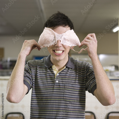 man holding a bra over his eyes