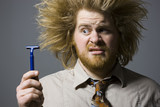 man with crazy hair holding a razor
