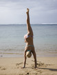 woman doing a handstand in a bikini