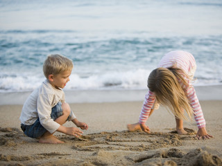 brother and sister playing in the sand at the beach
