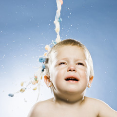 milk and cereal pouring onto a baby's head