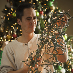 man untangling christmas tree lights