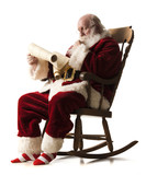 santa claus sitting in a rocking chair going over his list