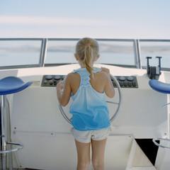 """""""USA, Utah, Lake Powell, Girl (6-7) at wheel of sailboat, rear view"""""""