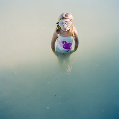 """USA, Utah, Lake Powell, Girl (6-7) standing in water and wearing scuba mask"""