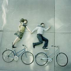 """USA, Utah, Salt Lake City, Couple lying holding hands and lying on pavements with their bikes"""