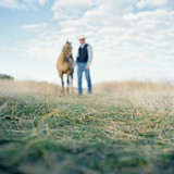 """USA, Utah, Mapleton, Cowboy standing with horse at pasture, focus on grass"""