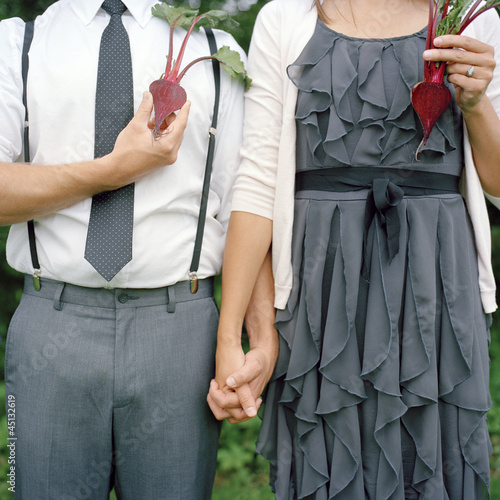 """USA, Utah, Salt Lake City, Young couple with halves of beetroots in place of heart, midsection"""