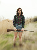 """USA, Utah, Orem, Portrait of young woman with rifle"""