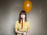 Studio shot of woman with balloon and party blower