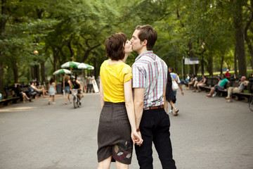 """USA, New York State, New York City, Young couple kissing in park"""