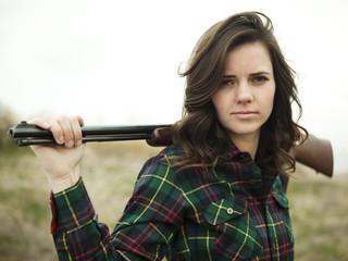 """USA, Utah, Orem, Portrait of young woman holding rifle"""