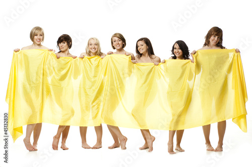 Studio shot of seven naked woman holding yellow material in front of them