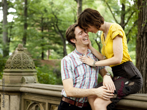 """USA, New York State, New York City, Young couple in park, woman sitting on railing"""