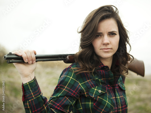 """USA, Utah, Orem, Portrait of young woman holding rifle"""