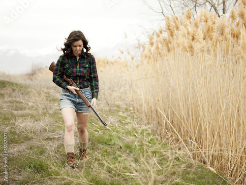 """USA, Utah, Orem, Woman with rifle walking on meadow"""