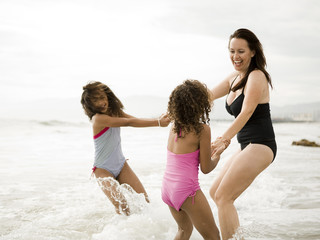 """USA, California, Los Angeles, Mother and daughters (6-11) playing on beach"""