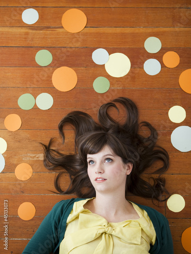Portrait of young woman against wooden background with decoration