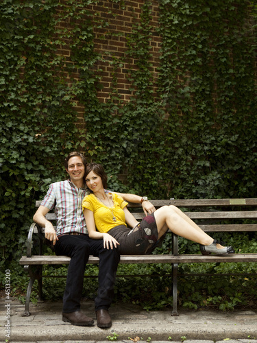 """USA, New York, New York City, Portrait of young couple on park bench"""