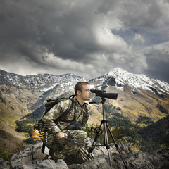 hunter using binoculars to spot prey