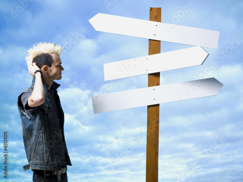 man looking at road sign