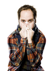 man wearing flannel blosing his nose
