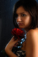 Girl in rain with red rose behind the window